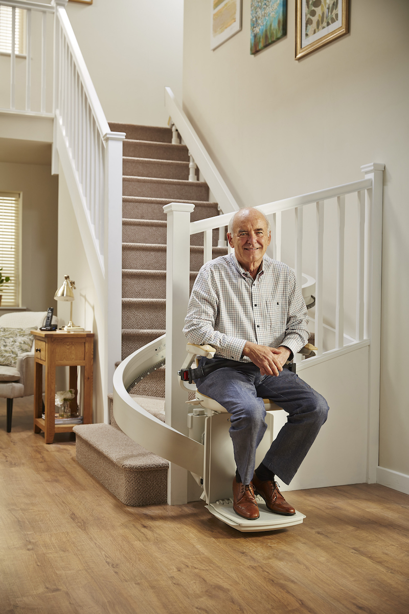 Man on a curved Acorn stairlift